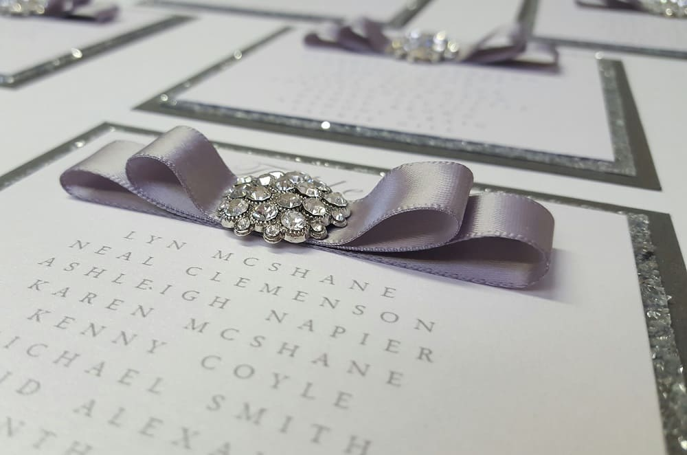 Wedding Business Dollybird Stationery Are Living The Dream At Storage Vault Work Space - close up of invite with silver glitter brooch